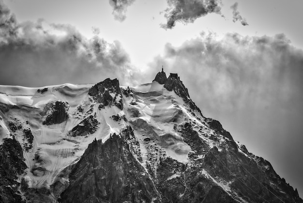 Grayscale shot of the famous aiguille du midi mountain covered with snow in france