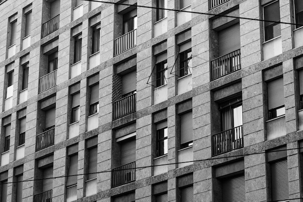 Grayscale shot of a long building with windows and balconies