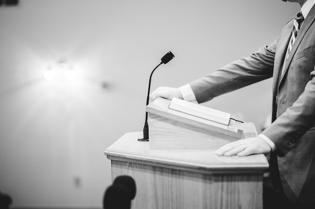 A grayscale shot of a male speaking at the podium