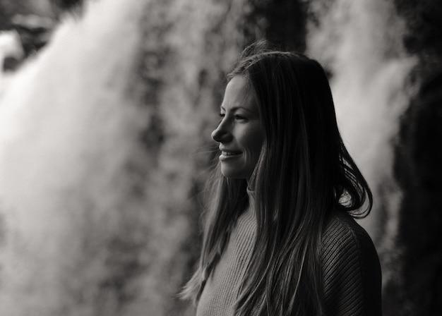 Снимок в оттенках серого: очаровательная кавказская женщина смотрит в сторону