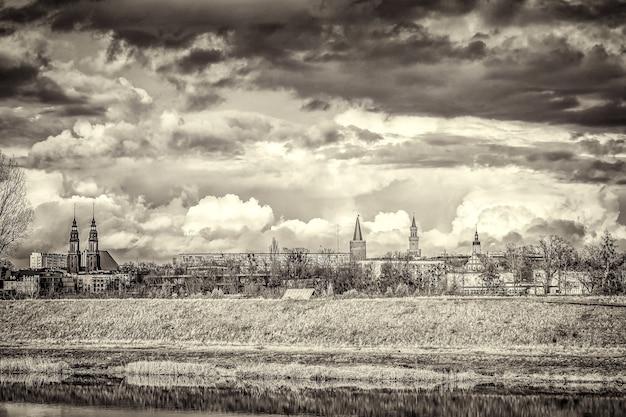 Снимок зданий вдалеке в оттенках серого под облачным небом