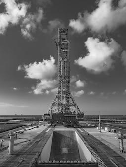 Снимок в оттенках серого башни, на которой установлена ракета sls, в космическом центре кеннеди.