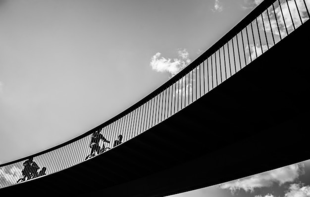 Grayscale shot of people riding bicycles on the bridge