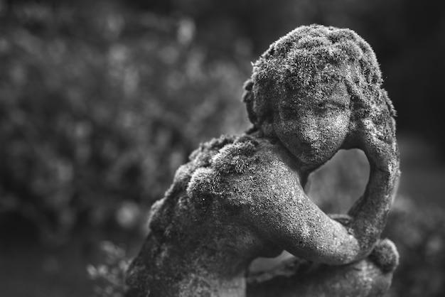 Colpo in scala di grigi di sculture in pietra in un giardino