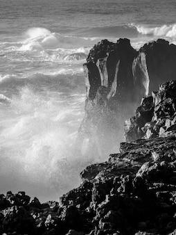 Colpo in scala di grigi di onde forti che colpiscono grandi rocce su una riva con spruzzi d'acqua e spruzzi