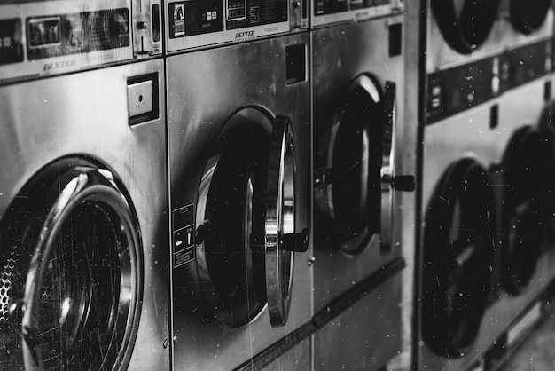 Grayscale shot of a washing machine with opened doors
