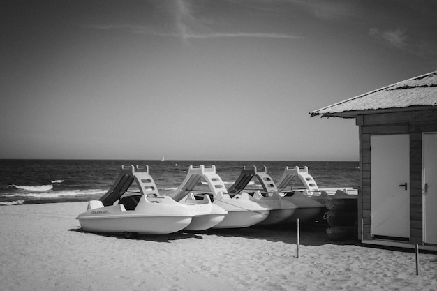 Grayscale shot of watercrafts or marine vessels near a cabin on a sandy beach
