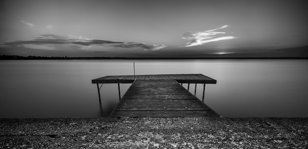 Grayscale shot of a wooden pathway over the sea under a clear sky
