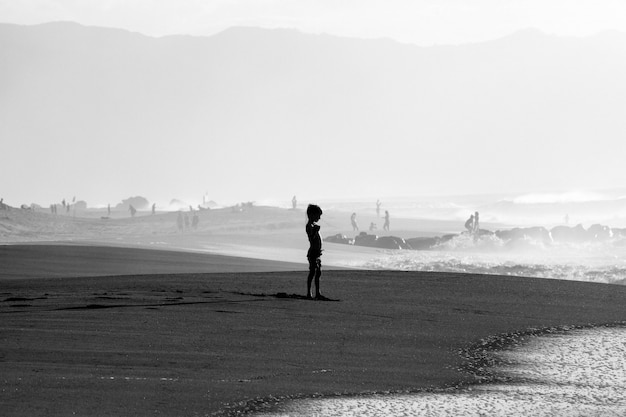 Grayscale shot of a young boy on a sandy seashore near the sea