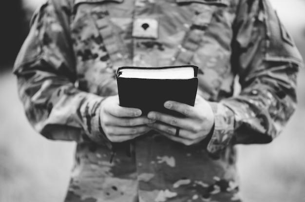 Colpo in scala di grigi di un giovane soldato che tiene una bibbia
