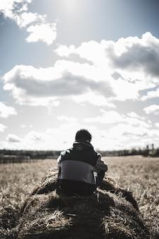 Vista in scala di grigi dell'uomo che si trova sull'erba da fieno