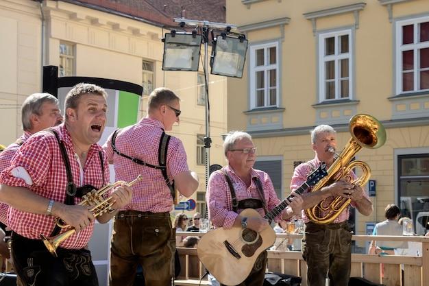 그라츠 / 오스트리아-2019 년 9 월 : 스티 리아 민속 문화의 연례 가을 축제 (aufsteirern). 마을 광장에서 민속 음악을 연주하는 밝은 전통 드레스를 입은 남자의 그룹.
