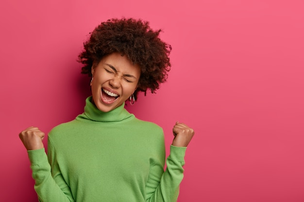 위대한 업적과 성공 개념. 행복한 아프리카 계 미국인 여성이 주먹을 쥐고, 승리의 몸짓을하고, 예 비명을 지르고, 머리를 기울이고, 녹색 터틀넥을 입습니다.