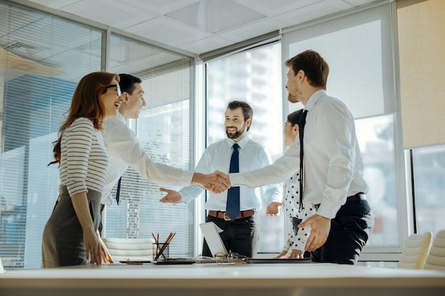 素晴らしい成果。成功したプロジェクトでお互いを祝福しながら、明るく笑顔でお互いに手を振る明るい若い従業員