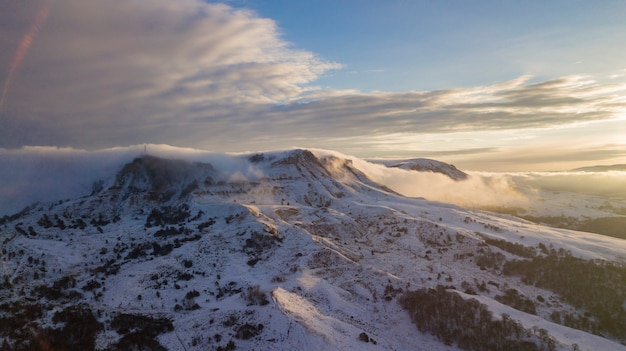 Great aerial landscape view of the snowy massive mountain in sunlight
