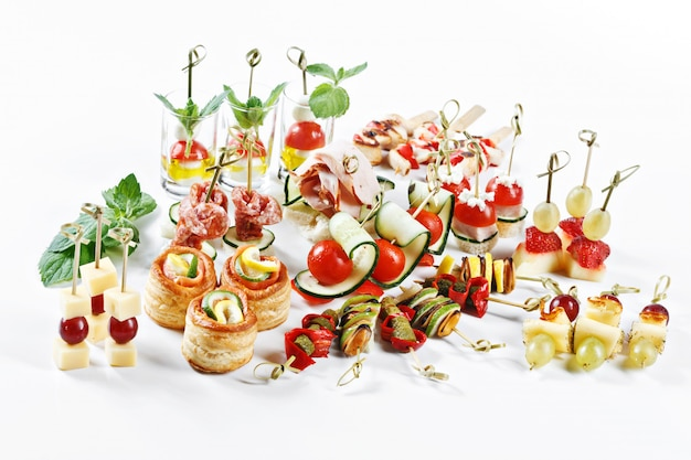 Great attractive set of canapes with vegetables, cheese, fruits, berries, salami, seafood, meat and decoration on white table