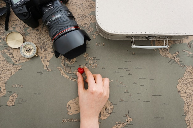 Great background with travel items and hand placing a heart