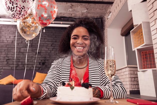 Отличная вечеринка по случаю дня рождения. веселая счастливая женщина сидит перед тортом, улыбаясь вам