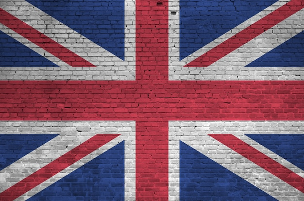 Great britain flag depicted in paint colors on old brick wall. textured banner on big brick wall masonry background