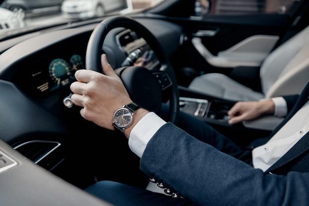멋진 차. 고급 차를 운전하는 동안 운전대에 손을 유지하고 있는 정장 차림의 젊은 남자의 꼭대기를 클로즈업