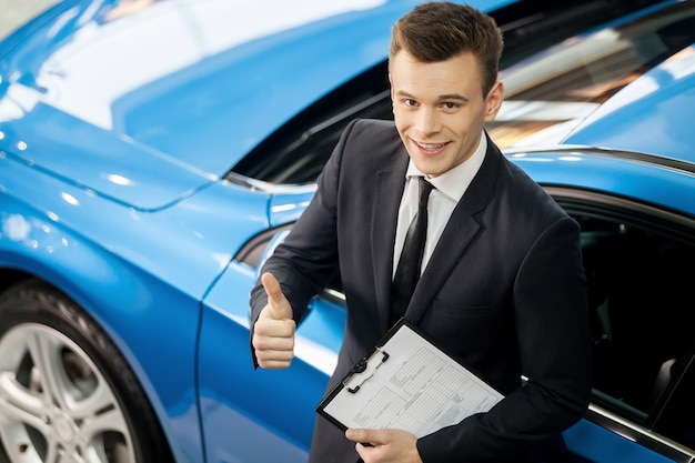 Great choose! top view of handsome young car salesman standing at the dealership with thumb up