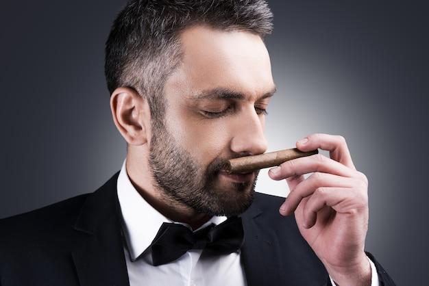 素晴らしい葉巻!葉巻の香りと灰色の背景に立っている間目を閉じたままの正装でハンサムな成熟した男の肖像画