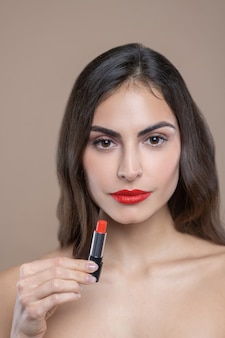 멋진 색, 립스틱. 갈색 눈과 밝은 빨간색 립스틱을 보여주는 머리를 가진 심각한 아름다운 젊은 여자
