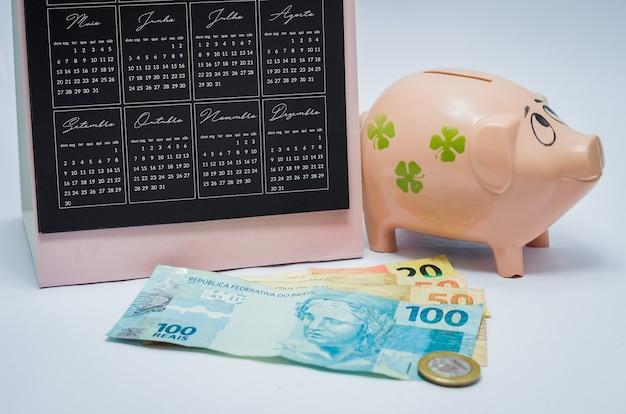 Great concept of economy, calendar, piggy bank, real brazilian money notes.