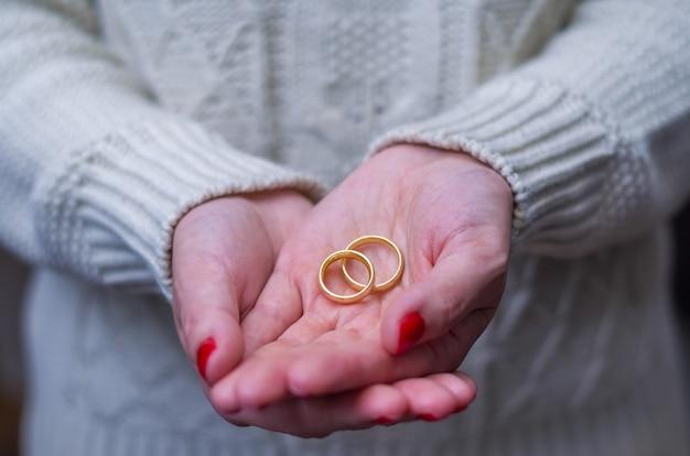 手に2つの金の結婚指輪と離婚女性の手の素晴らしいコンセプト。