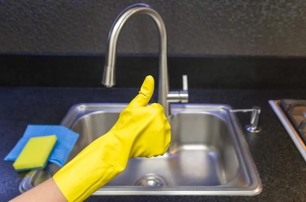 Отличная концепция домашней уборки, рука с перчаткой делает положительный знак большим пальцем.