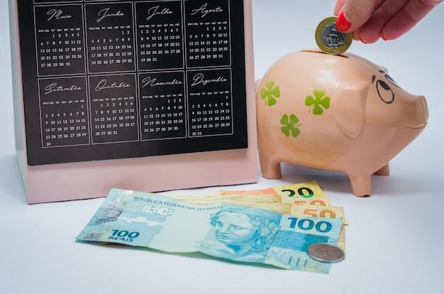 Отличная концепция экономики, календарь, копилка, реальные бразильские денежные знаки. рука женщины вставляя монету в копилку.