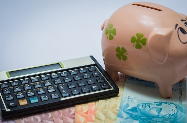 Отличная концепция экономики, финансовый калькулятор, копилка и бразильские реальные деньги.