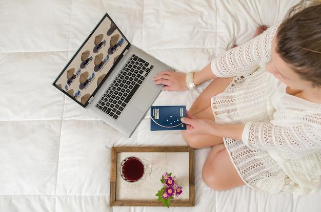 休暇の計画、休暇を計画する女性、手にパスポート、コンピューター、足を組んで、上から見て、ベッドでの素晴らしいコンセプト。