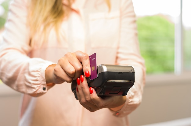 Great concept of payment with credit card, young caucasian woman making payment with credit card on machine.
