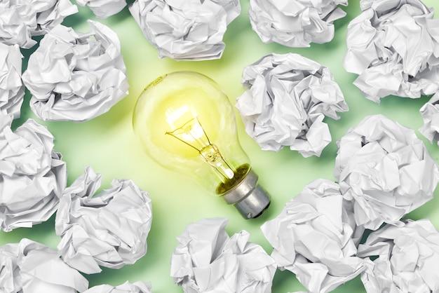 Отличная концепция с мятой офисной бумагой и лампочкой, стоящей на столе