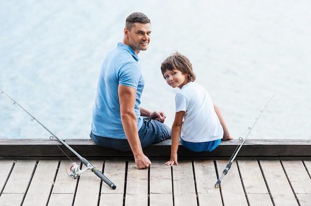 Отличный день для рыбалки. вид сзади отца и сына, сидящих на набережной и смотрящих через плечо, пока рядом с ними лежат удочки