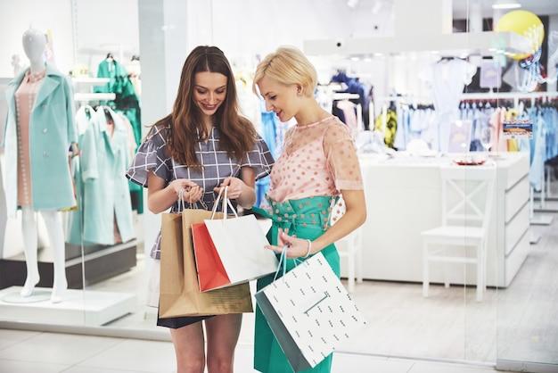 쇼핑하기 좋은 날. 두 명의 아름다운 여성이 가방을보고 그들이 산 것을 자랑합니다.