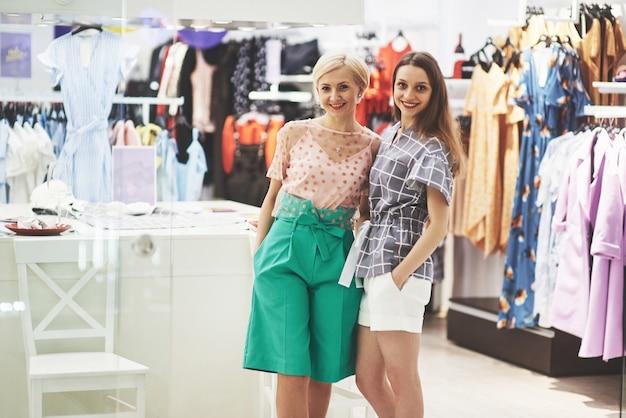 Отличный день для покупок. две красивые женщины с сумками смотрят друг на друга с улыбкой во время прогулки по магазину одежды.