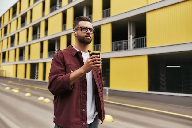 カジュアルな服装と使い捨てカップを保持している眼鏡の素晴らしい日ハンサムなひげを生やした男