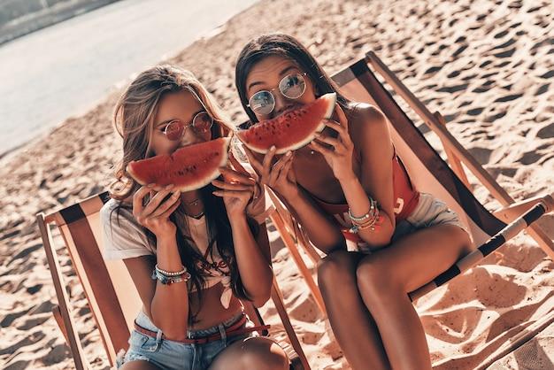 良い会社での素晴らしい一日。ビーチに座っている間、スイカのスライスで顔の半分を覆っている2人の魅力的な若い女性