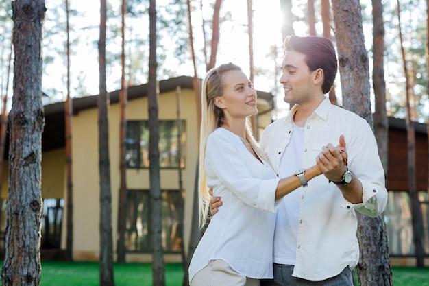 素晴らしい日。屋外で素晴らしい時間を過ごしながら一緒に立っているうれしそうな喜びのカップル