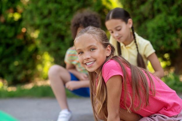Отличный день. радостная длинноволосая девушка в розовой футболке с друзьями в зеленом парке проводит свободное время в погожий день