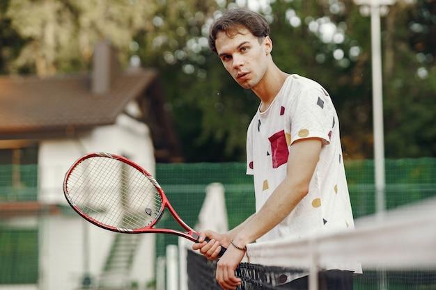 Ottima giornata per giocare! allegro giovane uomo in maglietta. ragazzo con racchetta da tennis e palla.