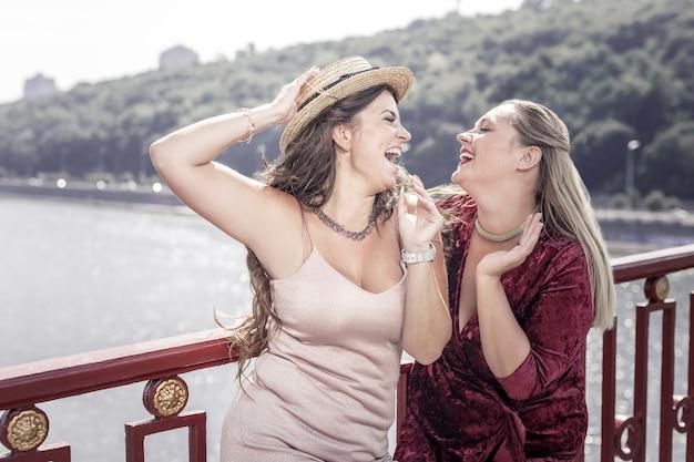 Отличный день. положительные радостные женщины смеются друг другу, стоя на мосту