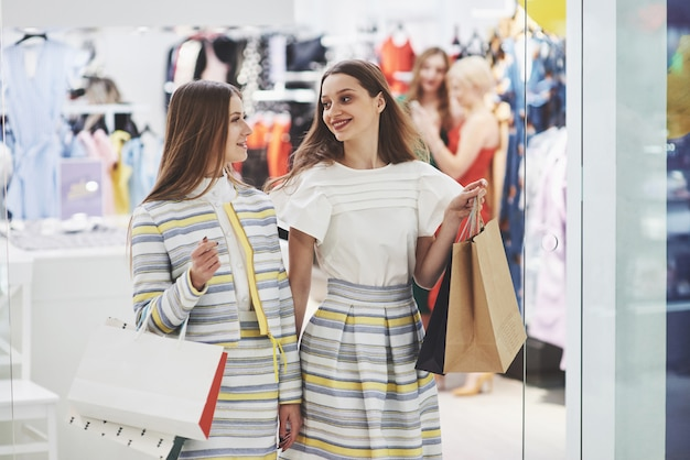 Great day for shopping. two beautiful women with bags looking at each other with smile while walking at the clothing store