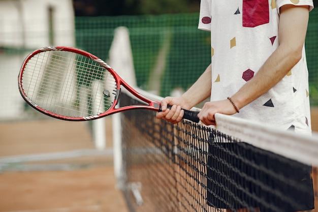 플레이하기 좋은 날! t- 셔츠에 쾌활 한 젊은 남자. 테니스 라켓과 공을 들고 남자입니다.