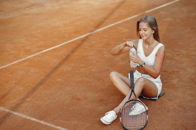 プレーするのに素晴らしい日です! tシャツを着た元気な若い女性。テニスラケットとボールを保持している女性。