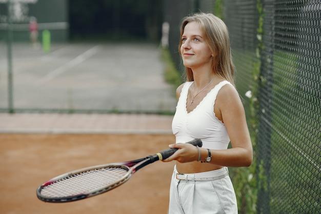 플레이하기 좋은 날! t- 셔츠에 쾌활 한 젊은 여자. 테니스 라켓과 공을 들고 여자입니다.