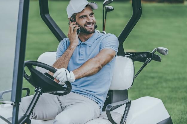 Отличный день для игры в гольф! красивый молодой улыбающийся человек за рулем тележки для гольфа и разговаривает по мобильному телефону