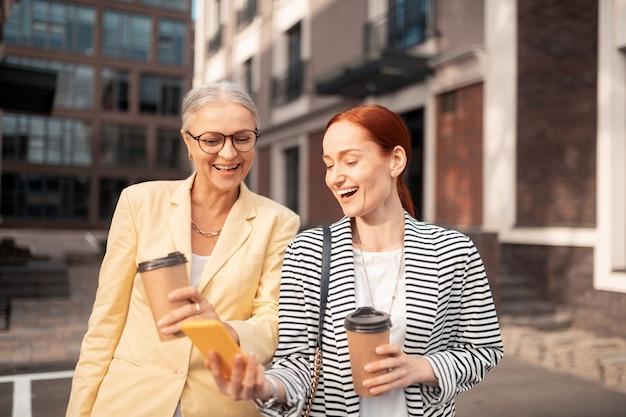 素晴らしい日。屋外に立って笑ってスマートフォンで写真を見ている2人のビジネス女性